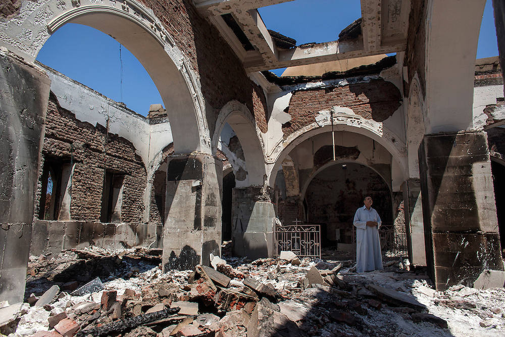 A Coptic Christian Egyptian man walks through the burned and looted Monastery of Emir Tadros church August 20, 2013 after a recent attack by Muslims in the village of Nazla, located near el Fayoum, around a 100 kilometers South of Cairo, Egypt.  Christian villagers report 2 churches and a monastery in the area came under attack by their Muslim neighbors on the same day as Egyptian security forces were moving to forcibly disperse the sit-in camp of the supporters of deposed president Mohamed Morsi.