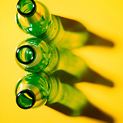 Green bottles on bright yellow background
