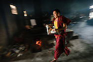 Tibetian Buddhist Munk is running with newspaper in a monastery kitchen in  India, on  April 11, 2015.<br />