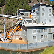 Yankee Fork Gold Dredge operated from 1940-1952 near near Custer Historic Site, in Idaho, USA. This floating gold dredge chewed a wide swath of stream gravel leaving rocky dredge tailings along 5.5 miles of the Yankee Fork, a tributary of the Salmon River, near Stanley, Idaho, USA. It recovered an estimated $1,037,322 in gold and silver at a cost of $1,076,100. Visit Land of the Yankee Fork State Park in Salmon-Challis National Forest near Stanley, Idaho. Panorama stitched from 2 overlapping photos.