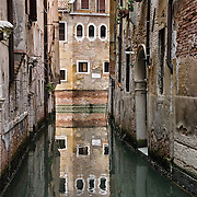 Old buildings reflect in a canal. Venice (Venezia), founded in the 400s AD, is capital of Italy's Veneto region, named for the ancient Veneti people from the 900s BC. The romantic City of Canals stretches across 100+ small islands in the marshy Venetian Lagoon along the Adriatic Sea, between the mouths of the Po and Piave Rivers. The Republic of Venice was a major maritime power during the Middle Ages and Renaissance, a staging area for the Crusades, and a major center of art and commerce (silk, grain and spice trade) from the 1200s to 1600s. The wealthy legacy of Venice stands today in a rich architecture combining Gothic, Byzantine, and Arab styles. Venice and the Venetian Lagoon are honored on UNESCO's World Heritage List.