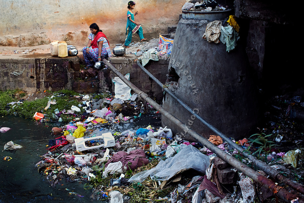 A girl is walking barefoot next to a woman collecting water from a broken municipal pipe running near a drain in Kasi Camp, one of the water-affected colonies standing close to the abandoned Union Carbide (now DOW Chemical) industrial complex in Bhopal, Madhya Pradesh, central India.