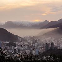 Clouds spill over the hills surrounding Rio de Janeiro at sunset.
