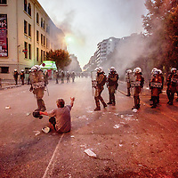 A man sits in the middle of the road pleading with riot police as over 17,000 cab drivers, students, and futbol fans marched in the northern port of Thessaloniki, Greece Sept 10, 2011. Marchers were protesting against austerity measures just before Prime Minister George Papandreou spoke.  Police were fired on by flare guns sticks and stones and even gas bombs, according to police representatives.  Photo Ken Cedeno
