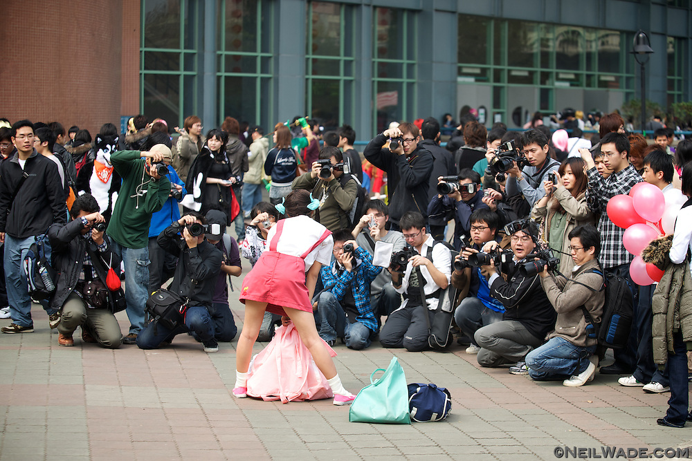 """A girl poses for a large crowd of photographers while dressed in a """"cosplay"""" costume at National Taiwan University in Taipei, Taiwan."""