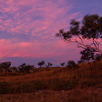 Australia, Northern Territory, Pink sunset colors clouds over Mabel Downs Cattle Station near Purnululu National Park