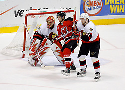 April 28, 2007; East Rutherford, NJ, USA; New Jersey Devils center Travis Zajac (19) and Ottawa Senators defenseman Andrej Meszaros (14) battle in front of Ottawa Senators goalie Ray Emery (1) during the first period of game two of the 2007 NHL Eastern Conference semi-finals at Continental Airlines Arena in East Rutherford, NJ.