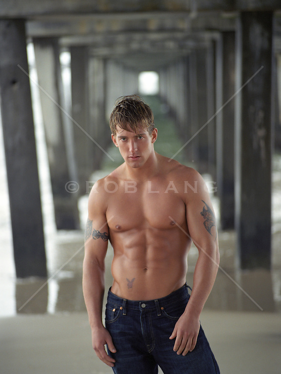 sexy shirtless man standing under a pier