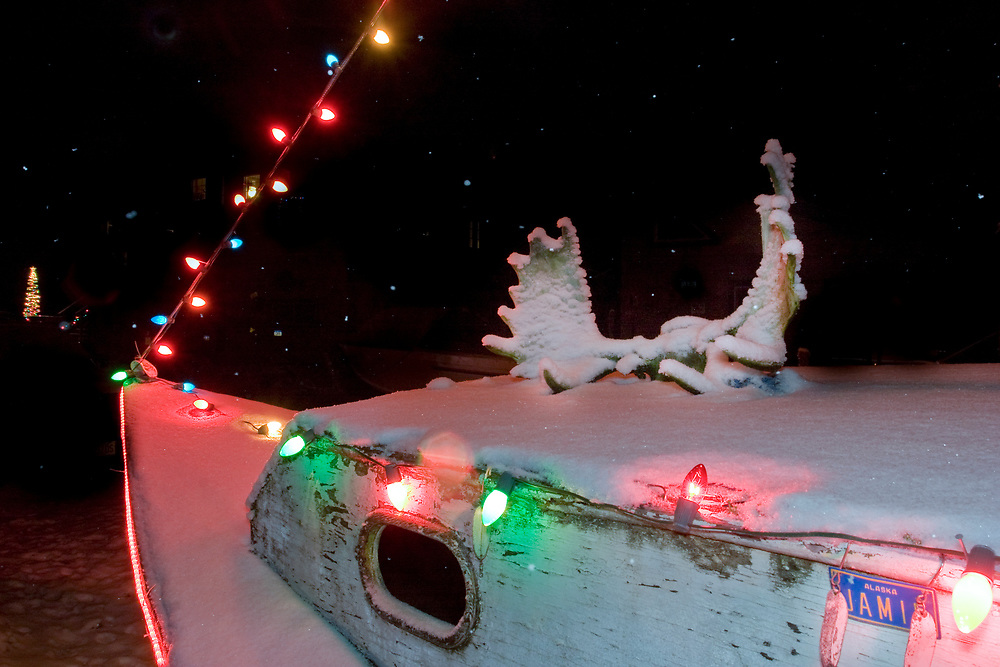 Snowy moose anlters adorn an old boat with colorful Christmas lights in the rigging.