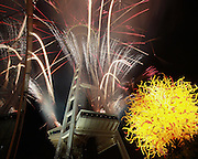 """Fireworks shoot from the Space Needle in Seattle at midnight on New Year's Eve, ringing in the new year. In the foreground at right is """"Pacific Sun,"""" a work on the grounds of Chihuly Garden and Glass. (Ken Lambert / The Seattle Times)"""
