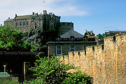 A view of Edinburgh Castle from the south of the castle, in the area of the Old Town.  Close-up of rocky cliff on which the castle was built and the foreground of a battlemented wall