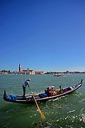 Tourists enjoying a gondola ride with Church of San Giorgio Maggiore in view, Venice, Italy