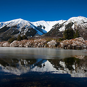 Purple Hill is reflected in the icy waters of Lake Pearson, located near Arthur's Pass, New Zealand.