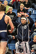 Christian Price congratulates a teammate after a match at the wrestling invitational they hosted.