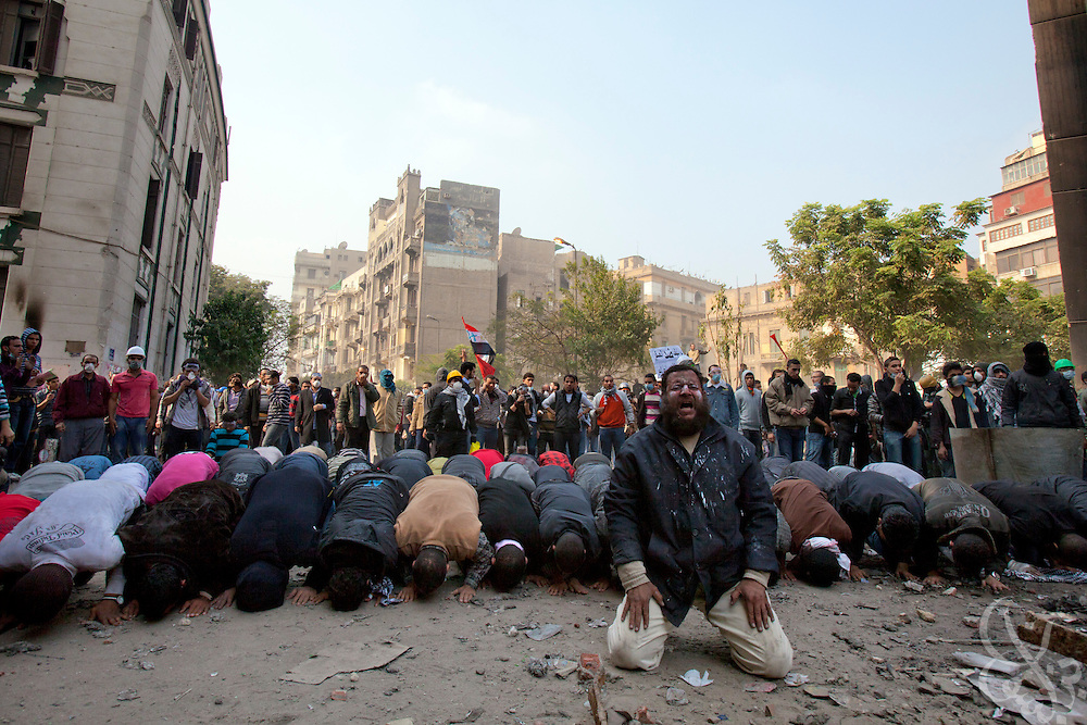 Egyptian protesters take advantage of a brief lull in clashes with nearby security forces to stop and pray November 22, 2011 near Tahrir square in central Cairo, Egypt. Thousands of protestors demanding the military cede power to a civilian government authority clashed with Egyptian security forces for a fourth straight day in Cairo, with hundreds injured and at least 29 protestors killed so far.  (Photo by Scott Nelson)