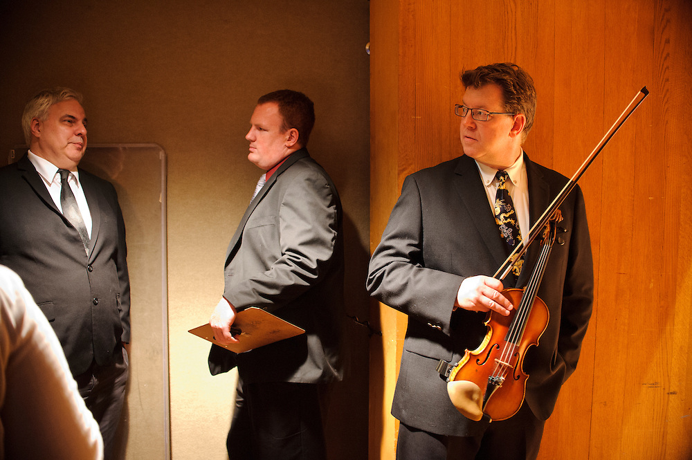 (photo by Matt Roth).Assignment ID: 30127886A..BSO Academy violin student Tim Topoleski waits by the door, next to Ennis Siebert, Meyerhof Symphony Hall stage manager, left, and Chris Monte, middle assistant personnel manager, before the start of the third annual BSO Academy's final performance at the Meyerhof Symphony Hall Saturday, June 30, 2012.