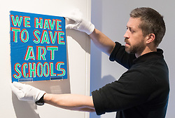 Christies, St James, London, March 4th 2016. A gallery technician hangs an artwork pleading the case for art in schools at the preview for the It&rsquo;s Our World charity auction at Christie's. Over 40 leading artists including David Hockney, Sir Antony Gormley, David Nash, Sir Peter Blake, Yinka Shonibare, Sir Quentin Blake, Emily Young and Maggi Hambling have committed artworks to the It&rsquo;s Our World Auction in support of The Big Draw and Jupiter Artland Foundation, to be sold at Christie&rsquo;s London on 10 March 2016.<br />  ///FOR LICENCING CONTACT: paul@pauldaveycreative.co.uk TEL:+44 (0) 7966 016 296 or +44 (0) 20 8969 6875. &copy;2015 Paul R Davey. All rights reserved.