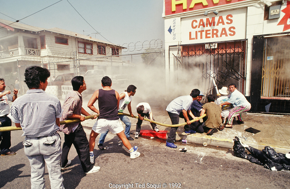 Several area residents attempt to put out a fire in the mostly hispanic area of Los Angeles, Pico/Union.
