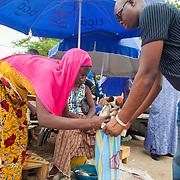 LÉGENDE: Rosine réalise une belle affaire en vendant ses poissons à un client. LIEU: Marché de Chagoua, N'Djaména, Tchad. PERSONNE(S): Rosine Remadsi (à gauche) légèrement courbée, client à droite et en arrière plan d'autres vendeuses assisent devant leurs étalages.