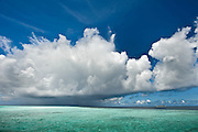 A Maldivian Island on the right side of the picture is about to be hit by a thunder shower approaching from the left. North Male Atoll. Maldives