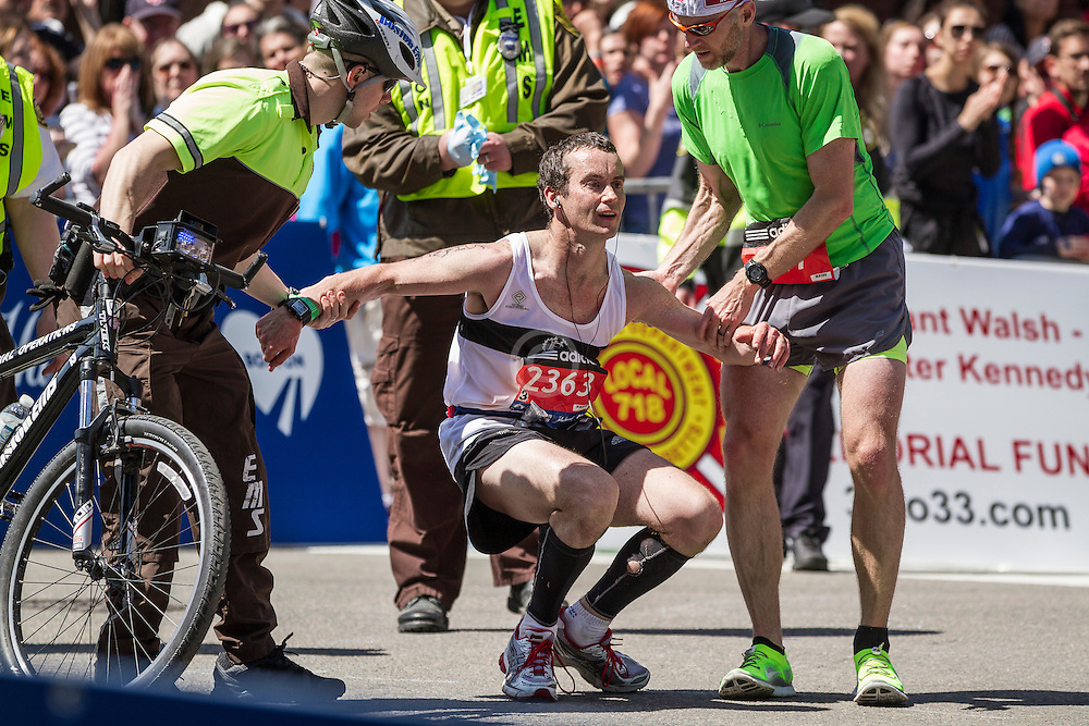 2014 Boston Marathon: runner  briefly passes out as medics attend to him