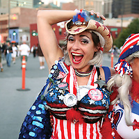 "A group of women outside the DNC dressed up as cartoonish patriotic girls ""from Crawford, Texas."" One holds a paper mache puppet with the likeness of Bush on one side and McCain on the other."