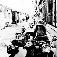 """BEIJING, HAIDIAN DISTRICT,CHINA-AUGUST15,1999:.a group of punks hang out together in the alley outside the Scream Club before a punk show, August 15, 1999, in China.. In the spring of 1998, a handful of youngsters teamed up to unofficially rebel against conformist Chinese life. They shaved their heads, and founded bands with names like """"Brain Failure"""" and """"Anarchy Boys"""".  To some like Punker Xiao Rong, this lifestyle was an extension of the life he'd begun as a school dropout at age sixteen.-Although the majority of the punks came from well-off families, they preferred to live in self-imposed poverty. .The Scream Bar and its surrounding dusty alleyways in the student district became the center of youthful rebellion until it was closed . The punks bands have moved on to other bars in Beijing, some got contracts with foreign record companies and even toured Europe, Japan and the US."""