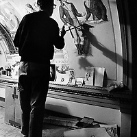 Capitol muralist Cliff Young paints details on a hallway ceiling in the U.S. Capitol while standing on a scaffolding.