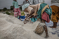 Tamil women harvest salt, using methods unchanged for centuries, from salt pans.  Throughout India wetlands are under threat from expanding cities and land use like these salt pans, even though it is a signatory nation of the Ramsar Convention on Wetlands.  Salt pans often encroach upon mangrove forests, the natural nursery for young fish which will replenish coastline fish stocks depleted by overfishing. <br /> <br /> India is the 3rd largest producer of salt in the world.  Wages are meagre for workers who find it hard to break the cycle of poverty.  Reflected light from the water filling salt pans cause eye problems for workers and it is said that, after workers die, their hands and feet are difficult to burn during cremation due to decades of salt absorbed into their skin.