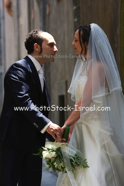 Italy, Sicily, A young bride and groom on their wedding day outside the church