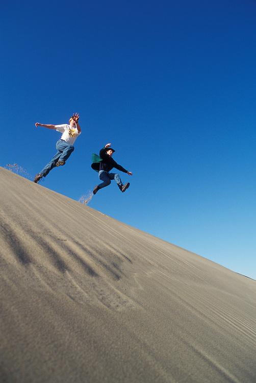 Two young men jumping off sand dune ridge; Oregon Dunes National Recreation Area, Umpqua Dunes section, Oregon coast.  .