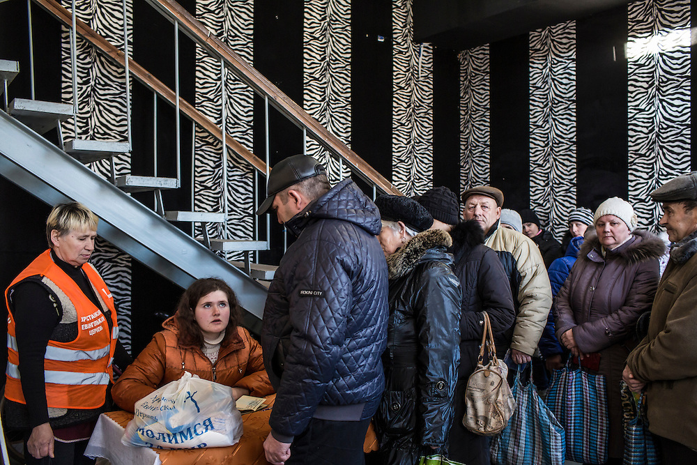 MARIINKA, UKRAINE - FEBRUARY 20, 2016:  Congregants at the Christian Help Center of the Church of the Transfiguration sign up to receive packages of food assistance in Mariinka, Ukraine. The Donetsk suburb has been the scene of some of the heaviest fighting recently between Ukrainian forces and pro-Russian rebels. CREDIT: Brendan Hoffman for The New York Times