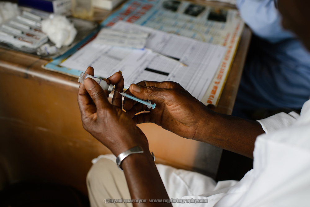 A health worker prepares a vaccine during vaccinations against tetanus and other diseases at a health centre in the village of Guiglo in western Cote d'Ivoire on 13 August 2012.