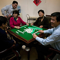 BEIJING, 25. JANUARY, 2009 :   Mr. Li's  relatives in the basement of his apartment on new years' eve  in Beijing .<br /> Mr. Li, a paper factory owner, is facing one of his most difficult times .&quot; Last November the market suddenly went down ,&quot; Li says.   <br /> He had bought paper, a lot of paper, and paid 7000 Yuan/ t .<br />  Li's company buys paper from paper mills and lives from the sales to publishing houses and other companies.  Since the market's collapse , he manages to sell the paper only for 6000 Yuan/t.<br /> His clients' export business to the USA had shrunk in Southern China. Mobile phone manufacturers don't need paper for the instruction guides to their mobile phones anymore as their US clients buys less China- made mobile phones.<br />  Toy manufacturers don't need paper anymore  because Americans import less toys from China. &quot; The crisis has driven many of my clients into bancruptsy&quot;, says Li.<br />  <br /> China's Communist Party  which will celebrate its 60th anniversary in October, currently faces its biggest challenge since the beginning of the economic reforms 30 years ago  : &quot; The phase of  rapid economic growth is over. For the first time the government is threatened with a  mistrust of a wide section of the population&quot;, warns the Communist party's Shang Dewen in Beijing.   <br /> Not only the China's poorest worry about the furture, but as well China's middle class is concerned about the crisis.     1,5 Millionen university graduates didn't find a job until the end of 2008  and this summer there'll be an additional  6,1 Million new graduates. More than 12 percent of university graduates face unemployment in 2009.