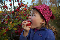 Jessica Laman eating a fresh apple in an apple orchard.