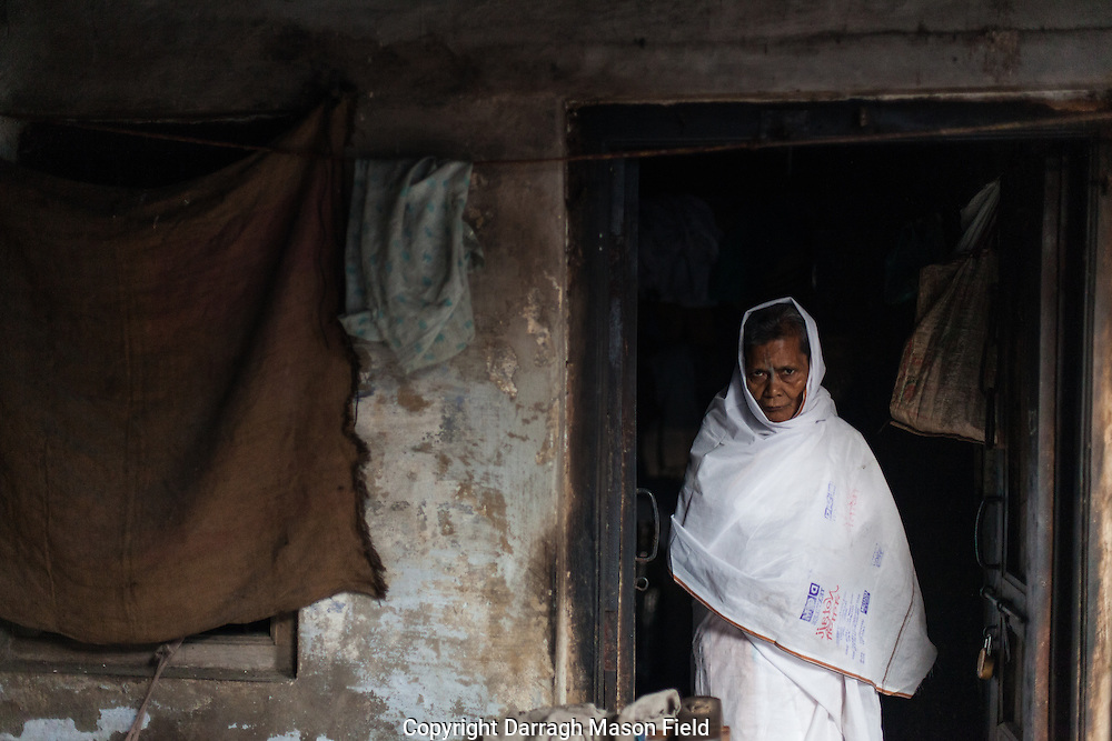 A widow from Kolkata dressed in the traditional white mourning colours  stands in the doorway of her shared lodgings.