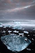 A blue iceberg on the beach at dusk at Jökulsárlón in South-East Iceland.