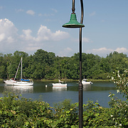 A railway light frames boats on the Connecticut River near the landing in Deep River, Connecticut.  This depot provides a connection between the Essex Steam Train and boat tours of the Connecticut River.