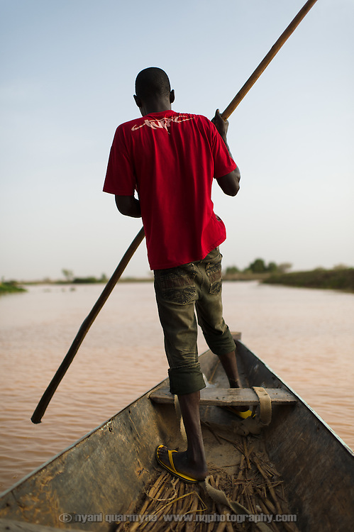 A boatman standing in the prow of a pirogue on the Niger River in the Tillabéri Region of Niger on 26 July 2013.