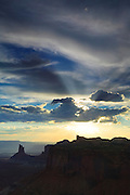 The sun shines through a hole in the clouds, forming crepuscular rays, also known as God beams, over the Green River as it flows through Canyonlands National Park, Utah. Crepuscular rays are beams of light that seem to originate from a single point.