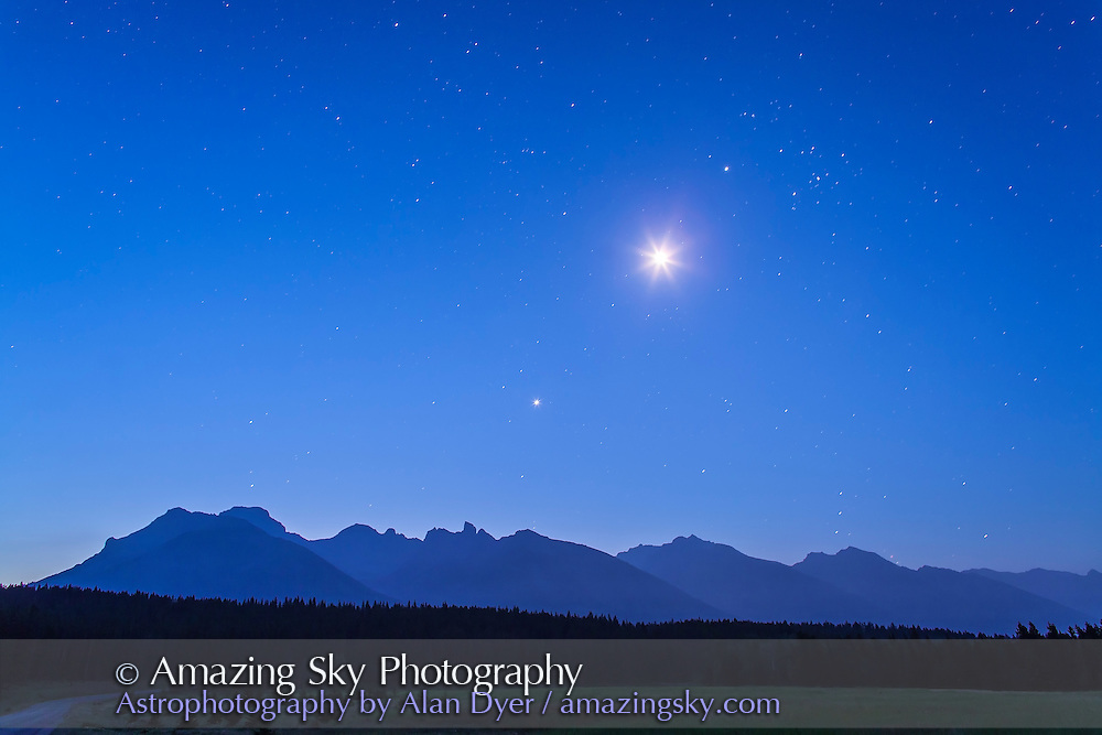 The waning crescent Moon (overexposed at centre) between Venus (below) and Jupiter (above) in the pre-dawn sky on the morning of Sunday, August 12, 2012. Jupiter is near Aldebaran and the Hyades. Orion is just rising over the mountains at right. Taken from the Minnewanka Loop road in Banff, with the Canon 5D MkII and 24mm lens for 30 seconds at f/4 and ISO 800.