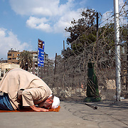 An Egyptian anti-government protester prays on a sidewalk outside the heavily guarded Orouba Presidential Palace February 11, 2011 in the Heliopolis district of Cairo, Egypt. Protesters marched Friday on a number of public buildings including the palace in an effort to spread their ongoing protests that are now in their 18th day. (Photo by Scott Nelson)