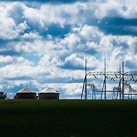 Traditional Mongolian yurts juxtaposed with modern electrical transmission lines, Inner Mongolia, China.