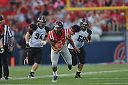 Mississippi quarterback Barry Brunetti (11) is chased by Southeast Missouri State's Jon Slania (68) and Southeast Missouri State's Travis Sanders (94) at Vaught-Hemingway Stadium in Oxford, Miss. on Saturday, September 7, 2013. (AP Photo/Oxford Eagle, Bruce Newman)