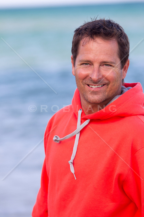 good looking forty something year old man in a bright colored sweatshirt at the beach