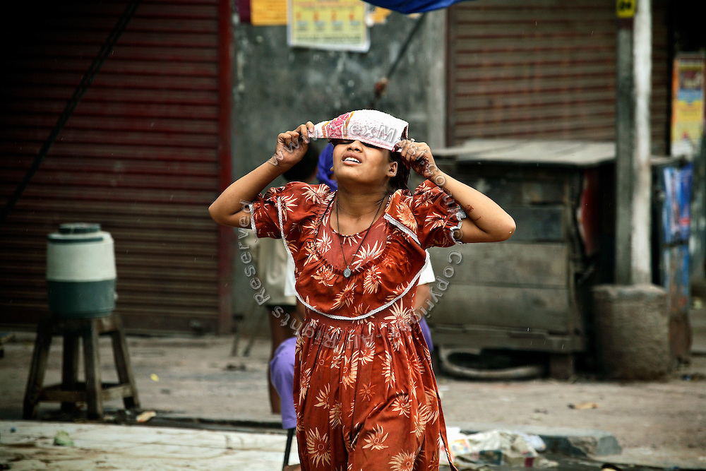 A young woman is covering her eyes during a sandstorm, in the heavily polluted city of Kanpur, Uttar Pradesh, the largest leather production hub in India.