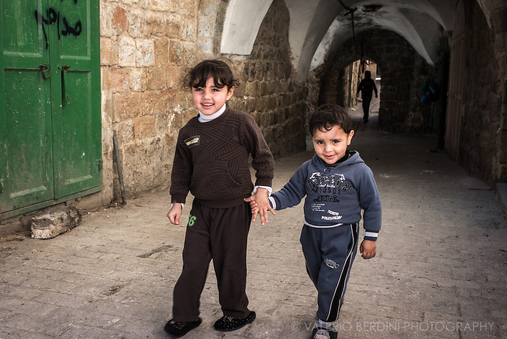 Palestinian children, in slippers, walk in a street of old Hebron allowed to Arabs.