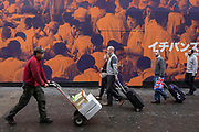 A delivery man walks past a construction hoarding featuring Asian canteen people in Chinatown, on 8th March 2017, London borough of Westminster, England.