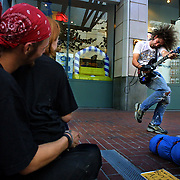 (LtoR) Nathan and his wife (doesn't want to be ID) enjoy a spontaneous street performance by Pedro while they solicit passers-by for money. Many like Nathan have regular spots they like to sit, here they are outside of Pioneer Place at the MAX station.