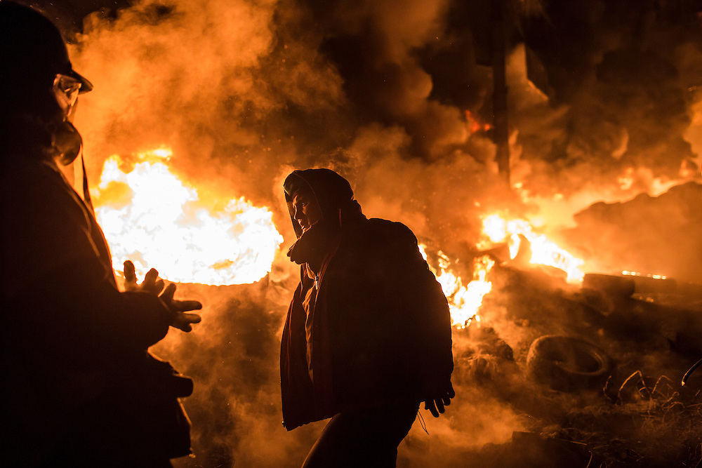 KIEV, UKRAINE - JANUARY 25: Anti-government protesters stand near burning tires during clashes with police on Hrushevskoho Street near Dynamo stadium on January 25, 2014 in Kiev, Ukraine. After two months of primarily peaceful anti-government protests in the city center, new laws meant to end the protest movement have sparked violent clashes in recent days. (Photo by Brendan Hoffman/Getty Images) *** Local Caption ***
